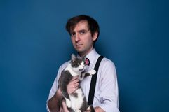 Handsome man in shirt, suspender and pink bow tie looking at camera and holding adorable grey cat. With white paws on blue background with copy space stock photos