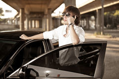 Handsome man in shirt talking on telephone by the car Stock Images