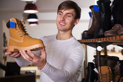 Handsome man in the shop. Handsome man wants to buy the shoe stock photos