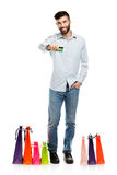 Handsome man with shopping bags and holding credit card Royalty Free Stock Photos