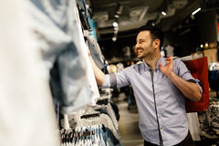 Handsome man shopping for clothes Stock Image