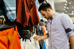 Handsome man shopping for clothes. Handsome man buying  new clothes Stock Photos