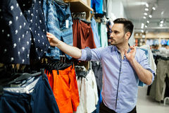 Handsome man shopping for clothes. Handsome man buying  new clothes Royalty Free Stock Photography