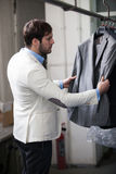 Handsome man shopping for clothes at a store. Stock Images
