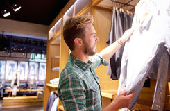 Handsome man shopping for clothes at store Royalty Free Stock Images