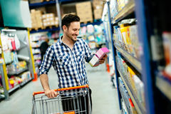Handsome man shopping in supermarket. Pushing trolley Royalty Free Stock Photos