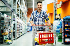 Handsome man shopping in supermarket. Pushing trolley Stock Images