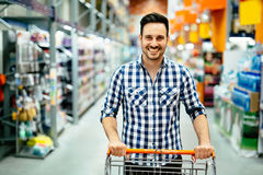 Handsome man shopping in supermarket. Pushing trolley Royalty Free Stock Images