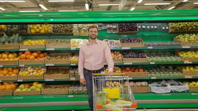 Handsome man with shopping trolley in a supermarket. Handsome man standing with shopping trolley in a supermarket stock video
