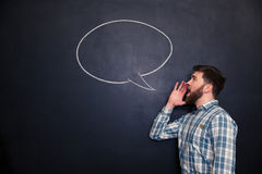 Handsome man shouting against chalkboard background with drawn speech bubble Royalty Free Stock Photos