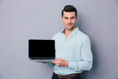 Handsome man showing blank laptop screen Stock Photography