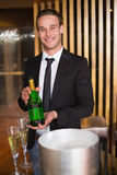 Handsome man showing champagne bottle Royalty Free Stock Images