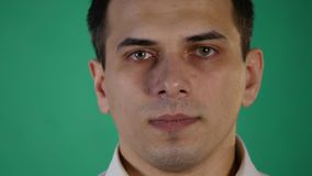 Handsome man showing different emotions. Close up. green background stock footage