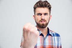 Handsome man showing fist at camera. Isolated on a white background Royalty Free Stock Image