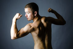Handsome man showing his muscles Royalty Free Stock Images
