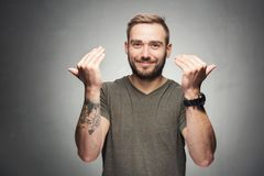Handsome man showing inviting gesture. Young handsome man raising his hands up. Inviting gesture Stock Image