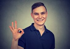 Handsome young man showing ok sign isolated on gray background. Handsome man showing ok sign hand gesture isolated on gray background Royalty Free Stock Photo