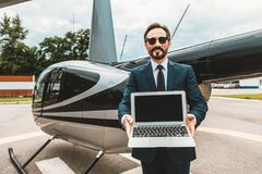 Handsome man showing the screen of his laptop and smiling. Attractive elegant businessman standing with the helicopter behind his back and smiling while showing royalty free stock photography