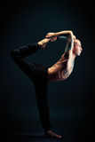 Plasticity. Handsome man shows different yoga exercises over black background Stock Photography