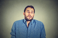 Handsome man shrugging shoulders showing ignorance. Closeup portrait young handsome man shrugging shoulders who cares so what I don't know gesture isolated on Stock Photography