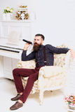 Handsome man singing in armchair Royalty Free Stock Photos