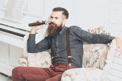 Handsome man singing in armchair Stock Photos