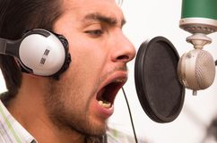 Handsome man singing in music studio Stock Images