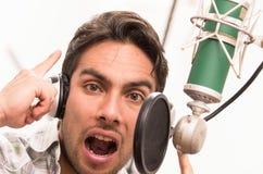 Handsome man singing in music studio Stock Images