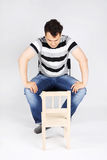 Handsome man sits on chair and looks at small chair Stock Photography