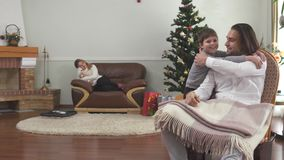 Handsome man sitting in arm-chair holding credit card. Little boy come and cuddle daddy. Happy family celebrates xmas at. Handsome man is sitting in arm-chair stock video footage