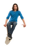 Handsome man sitting on a banner. Serious young man sitting on a banner with legs crossed at ankle. Full length studio shot isolated on white Stock Images