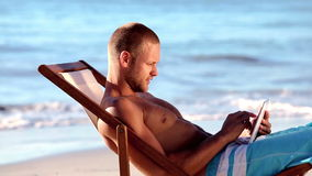 Handsome man sitting on the beach Stock Photography