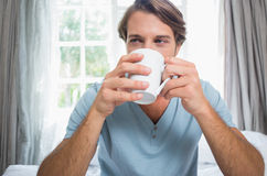 Handsome man sitting on bed drinking coffee Royalty Free Stock Image