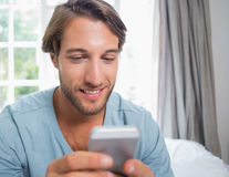 Handsome man sitting on bed sending a text message Royalty Free Stock Photos