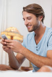 Handsome man sitting on bed texting on the phone Stock Photo