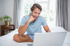 Handsome man sitting on bed using laptop smiling at camera Stock Photography