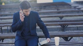 Handsome man sitting on the bench, using tablet and smartphone 4K. Handsome man sitting on the bench, using tablet and speaking on smartphone 4K stock footage