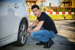 Handsome Man Sitting Besides the Wheel of Car. Handsome Young Man in Casual Clothing Squatting Besides the Wheel of a his White Car Changing Tires While Looking Stock Photo