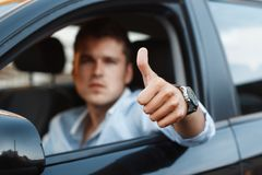 Handsome man sitting in a car and holding thumbs up Royalty Free Stock Photography