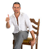 Handsome man sitting on a chair and showing ok sign Royalty Free Stock Image