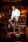 Handsome man sitting on chair on stage Royalty Free Stock Image
