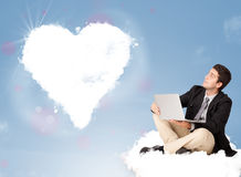 Handsome man sitting on cloud with heart Stock Images