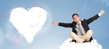 Handsome man sitting on cloud with heart Royalty Free Stock Photos