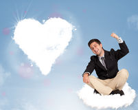 Handsome man sitting on cloud with heart Royalty Free Stock Photo