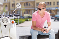 Handsome man sitting with coffee near his scooter Royalty Free Stock Photography