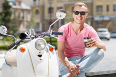 Handsome man sitting with coffee near his scooter Royalty Free Stock Image