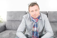 Handsome man sitting comfortably on couch. Handsome man sitting comfortably on a grey couch Royalty Free Stock Photos