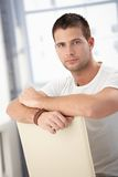 Handsome man sitting conversely on chair Stock Photos