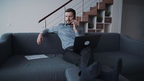 Handsome man is sitting on couch listening and checking new information about business stock footage