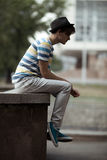 Handsome man sitting on the curb in city Royalty Free Stock Images